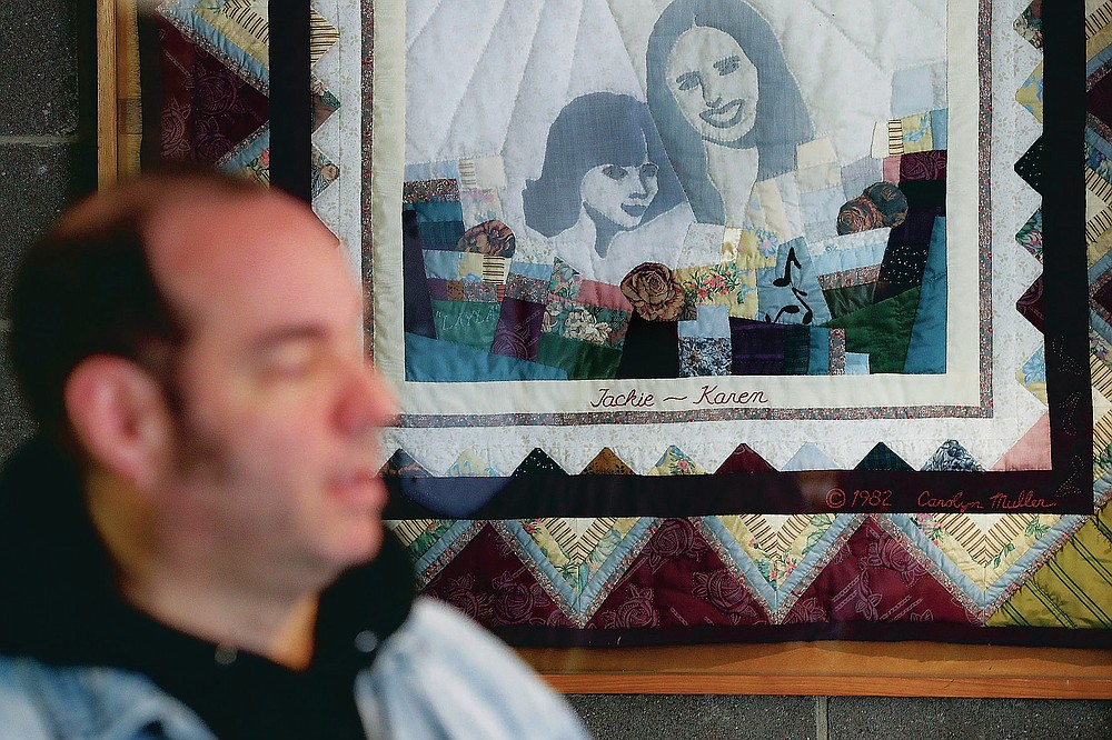 FILE-In this Thursday, Nov. 21, 2019 file photo, Fred Wittenbaum, of the P.E.M. scholarship that memorializes the three Finneytown students killed in a stampede at The Who's Dec. 3, 1979 concert, is interviewed beside a quilted memorial to the dead at the Finneytown High School secondary campus, in Finneytown, Ohio. Every year, Finneytown alumni hold a memorial scholarship fundraising event to honor their three classmates. In 2020, because of the coronavirus, they organized a show of prerecorded video interviews with The Who's frontman, Roger Daltrey, guitarist-songwriter Pete Townshend and a mix of recorded and live discussions with relatives of the 11 people killed on Dec. 3, 1979. (AP Photo/John Minchillo, File)