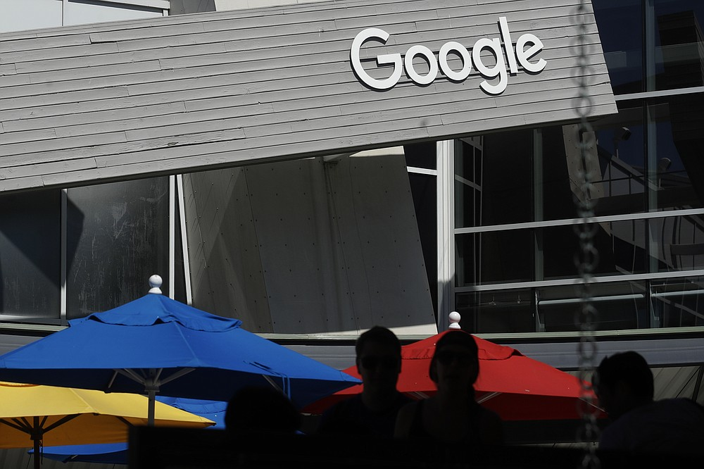 In this Sept. 24, 2019, file photo people walk by a Google sign on the company's campus in Mountain View, Calif. A group of 35 states as well as the District of Columbia and the territories of Guam and Puerto Rico filed an anti-trust lawsuit against Google on Thursday, Dec. 17, 2020, alleging that the search giant has an illegal monopoly over the online search market that hurts consumers and advertisers. The lawsuit, announced by Colorado Attorney General Phil Weiser, was filed in federal court in Washington, D.C. by states represented by bipartisan attorneys general. (AP Photo/Jeff Chiu, File)