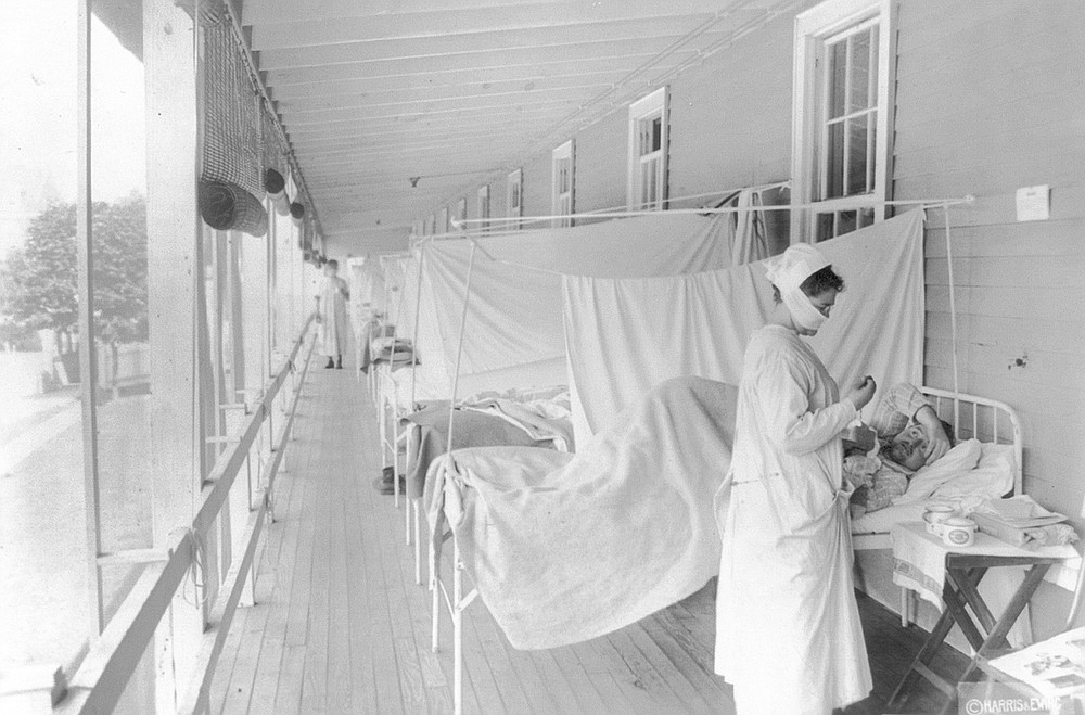 FILE - In this November 1918 photo made available by the Library of Congress, a nurse takes the pulse of a patient in the influenza ward of the Walter Reed hospital in Washington. In 1918, tens of thousands of U.S. soldiers died in World War I and hundreds of thousands of Americans died in a flu pandemic. Deaths rose 46% that year, compared with 1917. (Harris & Ewing/Library of Congress via AP, File)