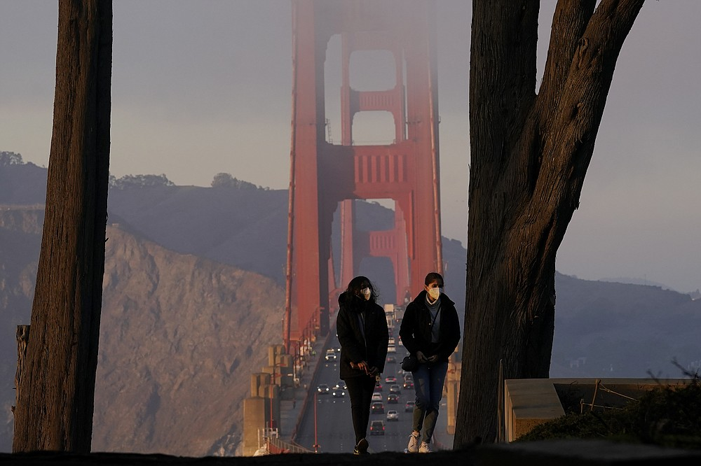 People wear face masks while walking upstairs at the Golden Gate Overlook in the Presidio in front of traffic driving on the Golden Gate Bridge during the coronavirus pandemic in San Francisco, Monday, Dec. 21, 2020. (AP Photo/Jeff Chiu)
