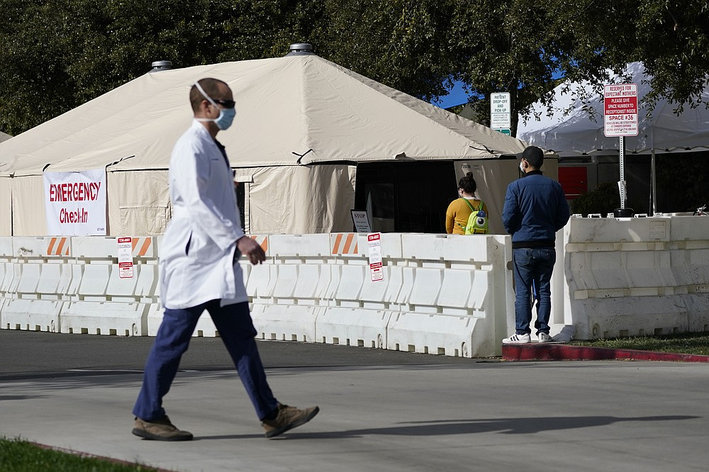 FILE - In this Dec. 17, 2020, file photo, a medical worker passes a medical tent outside the emergency room at UCI Medical Center in Irvine, Calif. California is desperately searching for nurses, doctors and other medical staff, perhaps from overseas, to meet demands as the coronavirus surge pushes hospitals across the state to the breaking point. With many of the state's hospitals running out of capacity to treat the severest cases, the state has brought in and deployed more than 500 extra staff but it needs a total of 3,000 temporary medical staff members. (AP Photo/Ashley Landis, File)