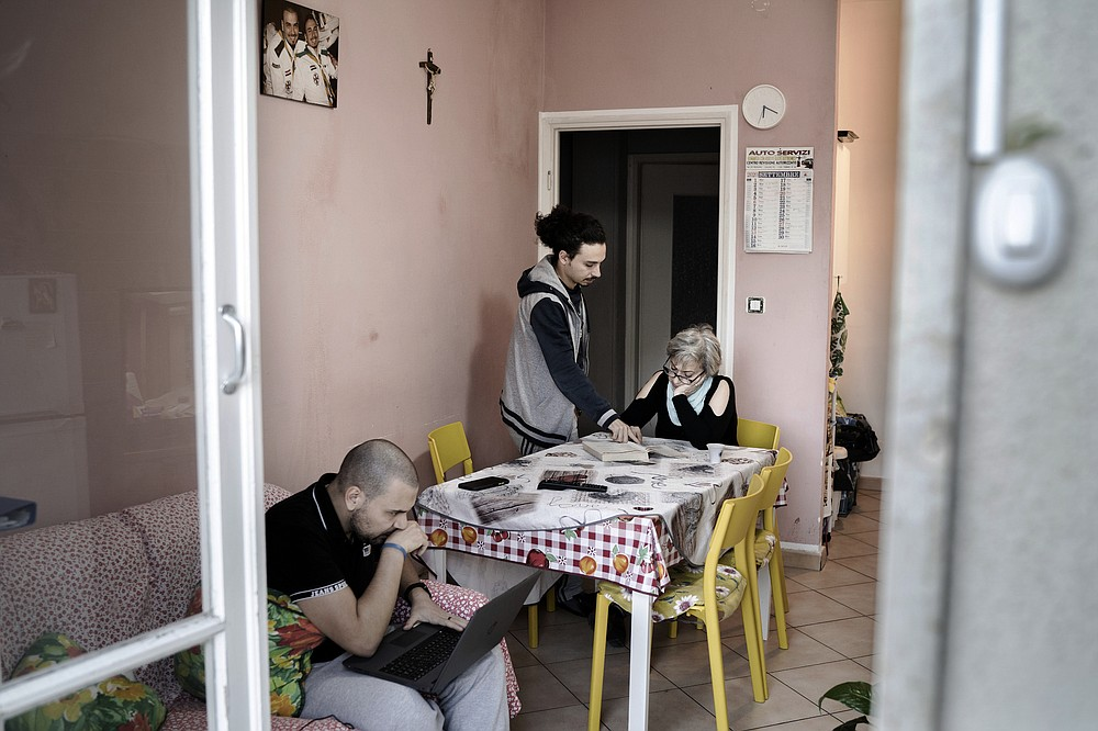 Antoine Khoury helps his mother, Maha Dahine, study Italian while brother Hanna Khoury works on a laptop in their apartment in Pinerolo, Italy, in September, after they fled Syria and previously spent two years in Lebanon. (The New York Times/Alessandro Grassani)
