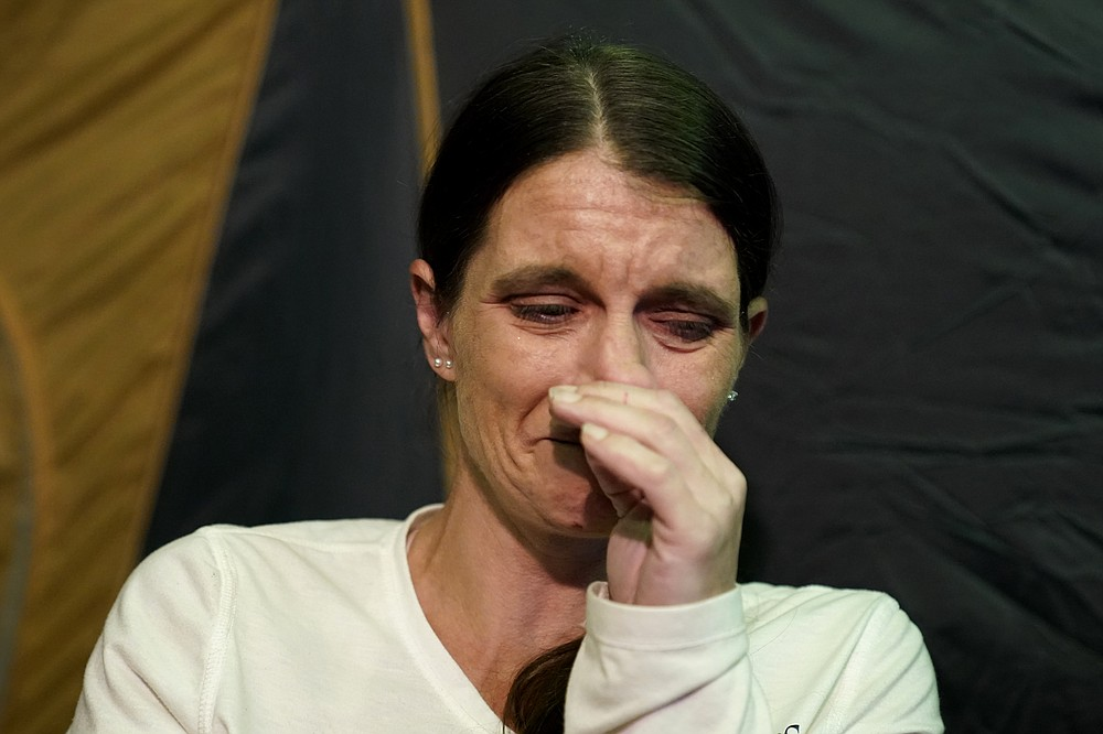Cristin Trahan cries inside a tent where she now lives with her husband, where their home once stood, in the aftermath of Hurricane Laura and Hurricane Delta, in Lake Charles, La., Friday, Dec. 4, 2020. (AP Photo/Gerald Herbert)