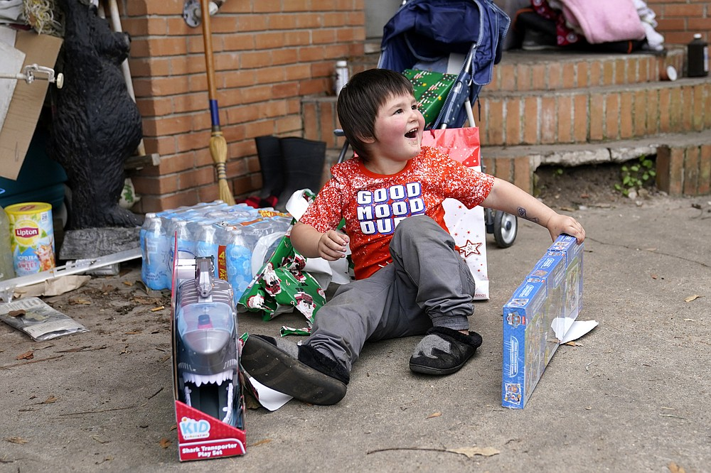 Conner Bourque reacts as he opens Christmas presents brought by church volunteers, where he lives with his family in a camper outside their heavily damaged home, in the aftermath of Hurricane Laura and Hurricane Delta, in Lake Charles, La., Friday, Dec. 4, 2020. (AP Photo/Gerald Herbert)