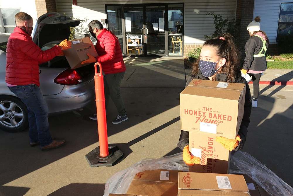 Leilani Ocasio, with the Northwest Arkansas Food Bank, distributes food Tuesday, Dec. 22, 2020, at the Siloam Springs Senior Activity and Wellness Center during a Northwest Arkansas Food Bank pop-up food pantry.  (NWA Democrat-Gazette/David Gottschalk)