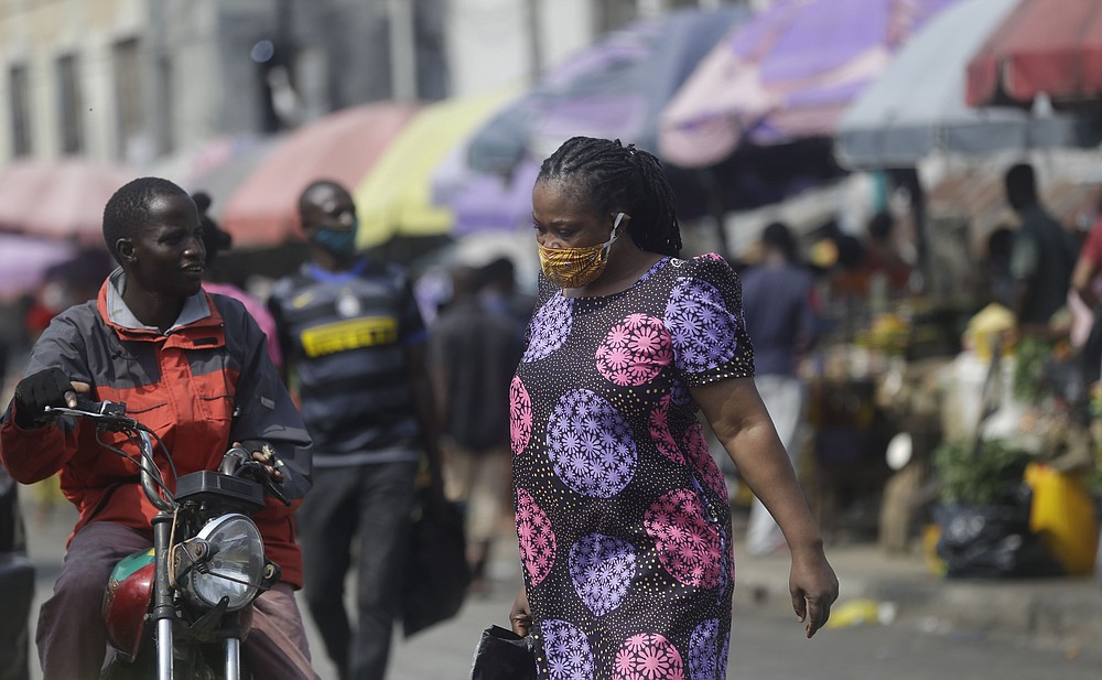 A woman wearing a face mask to protect against coronavirus, walks at a market in Lagos, Nigeria, Thursday Dec. 24, 2020. Africa's top public health official says another new variant of the coronavirus appears to have emerged in Nigeria, but further investigation is needed. The discovery could add to new alarm in the pandemic after similar variants were announced in recent days in Britain and South Africa and sparked the swift return of travel restrictions. (AP Photo/Sunday Alamba)