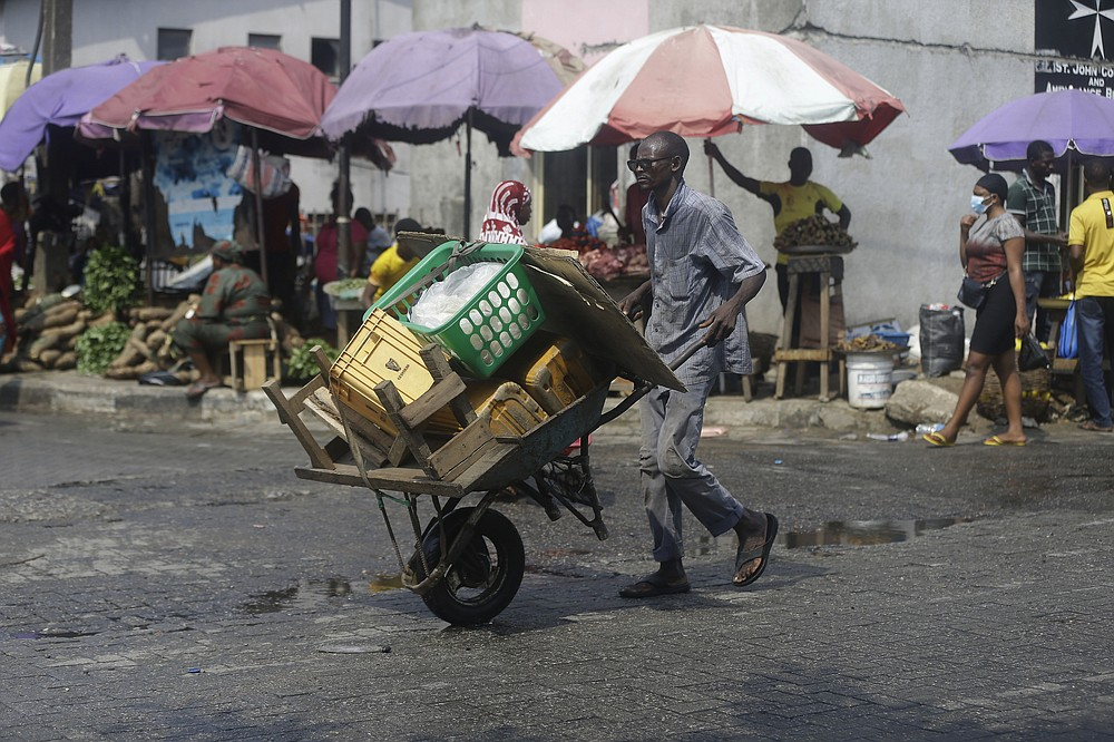 A man pushes a wheelbarrow, at a market in Lagos, Nigeria, Thursday Dec. 24, 2020. Africa's top public health official says another new variant of the coronavirus appears to have emerged in Nigeria, but further investigation is needed. The discovery could add to new alarm in the pandemic after similar variants were announced in recent days in Britain and South Africa and sparked the swift return of travel restrictions. (AP Photo/Sunday Alamba)