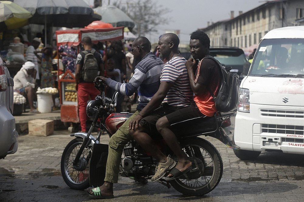 Men ride a bike, at a market in Lagos, Nigeria, Thursday Dec. 24, 2020. Africa's top public health official says another new variant of the coronavirus appears to have emerged in Nigeria, but further investigation is needed. The discovery could add to new alarm in the pandemic after similar variants were announced in recent days in Britain and South Africa and sparked the swift return of travel restrictions. (AP Photo/Sunday Alamba)