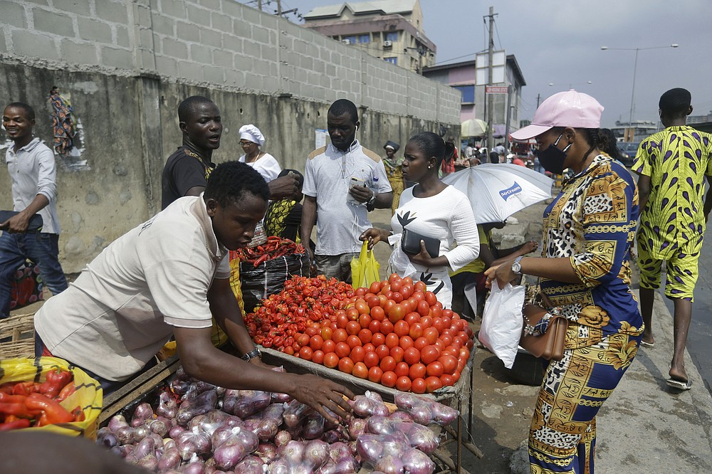 People buy vegetables, at a market in Lagos, Nigeria, Thursday Dec. 24, 2020. Africa's top public health official says another new variant of the coronavirus appears to have emerged in Nigeria, but further investigation is needed. The discovery could add to new alarm in the pandemic after similar variants were announced in recent days in Britain and South Africa and sparked the swift return of travel restrictions. (AP Photo/Sunday Alamba)