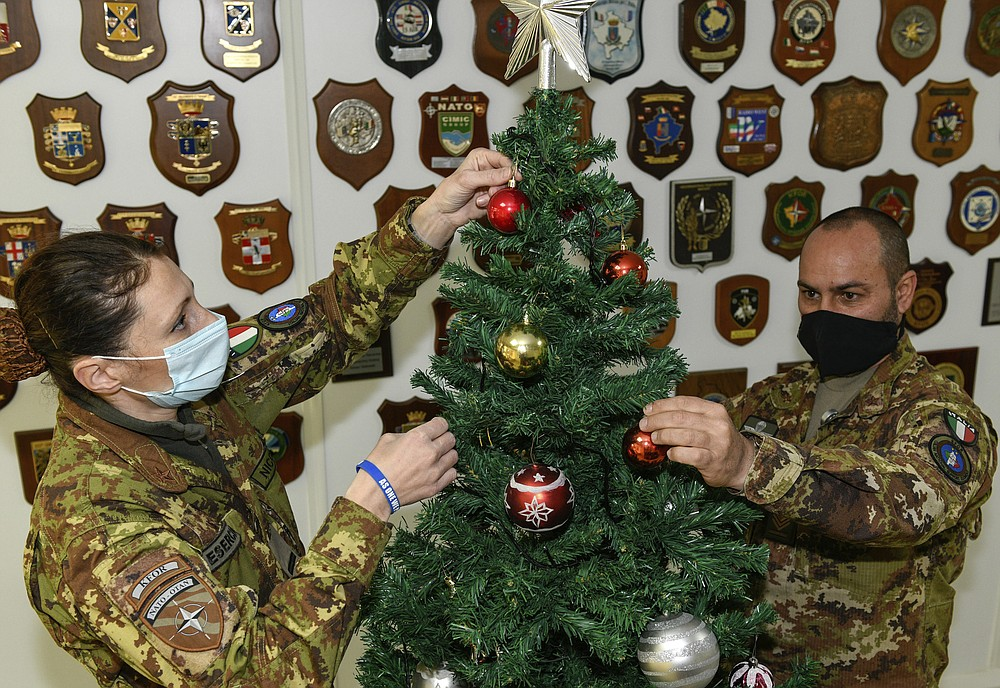 In this photo provided by NATO-led peacekeeping mission in Kosovo (KFOR), Italian soldiers decorate Christmas tree on the Christmas Eve in the KFOR military headquarters in Kosovo capital Pristina, Thursday, Dec. 24, 2020. The coronavirus pandemic has totally changed Christmas time operation method and celebrations for the Kosovo Force but it has left unchanged its mission: keeping Kosovo safe and secure for 22 years now on. (KFOR via AP)