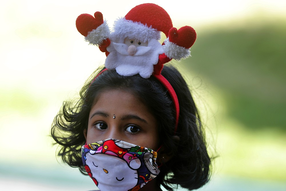 A Sri Lankan Christian girl wears a Santa hair band and a face mask as a precaution against the coronavirus as she arrives at a church to attend the Christmas mass in Colombo, Sri Lanka, Friday, Dec. 25, 2020. (AP Photo/Eranga Jayawardena)