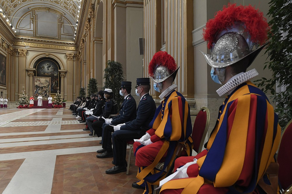 Pope Francis, background second from left, delivers the Urbi et Orbi (Latin for 'to the city and to the world' ) Christmas' day blessing inside the blessing hall of St. Peter's Basilica, at the Vatican, Friday, Dec. 25, 2020. (Vatican Media via AP)