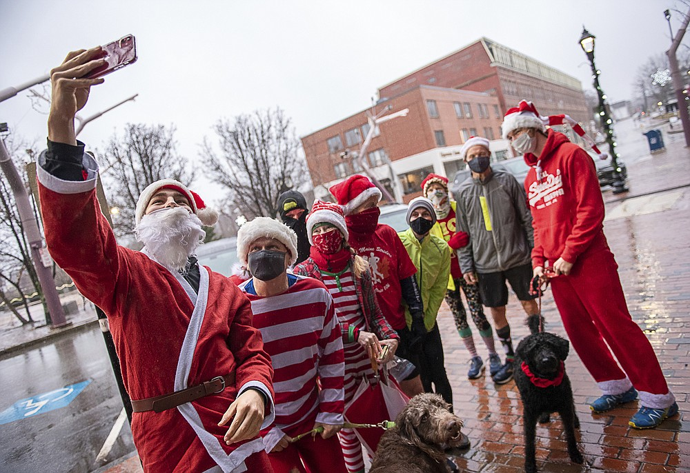 Maxi Kolb, an exchange student from Germany, takes a photo of a group of Santas and elves getting ready for their annual Christmas morning run on Main Street in Auburn, Maine on Friday, Dec. 25, 2020. The group gets together every Christmas morning and runs a loop through Lewiston Auburn. (Andree Kehn/Sun Journal via AP)