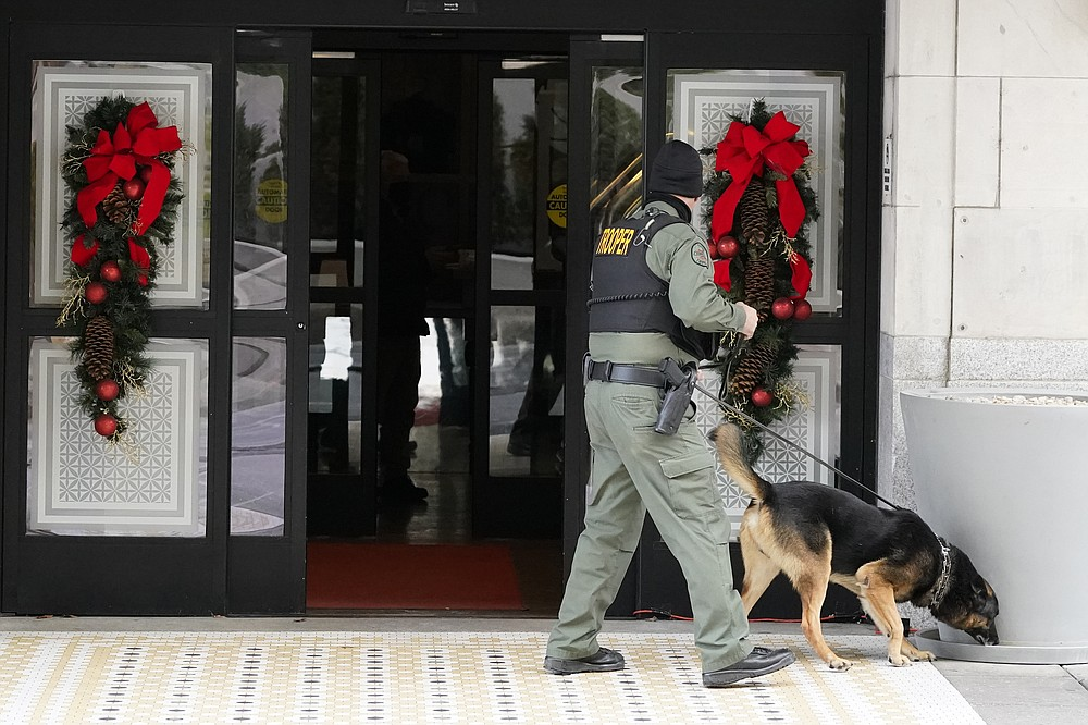 A K-9 team works in the area of an explosion in downtown Nashville, Tenn., Friday, Dec. 25, 2020. Buildings shook in the immediate area and beyond after a loud boom was heard early Christmas morning.(AP Photo/Mark Humphrey)