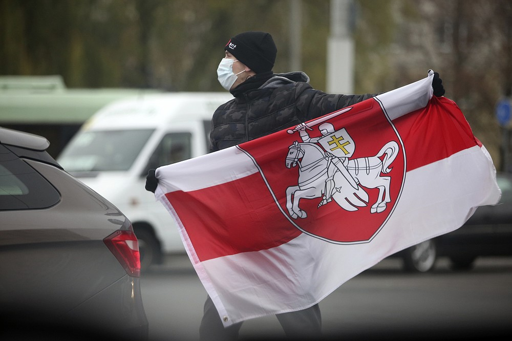 FILE In this file photo taken on Sunday, Nov. 22, 2020, A man wearing a face mask to help curb the spread of the coronavirus holds an old Belarusian national flag during an opposition rally to protest the official presidential election results in Minsk, Belarus. A wave of COVID-19 has spread through Belarusian jails packed with people imprisoned for taking part in four months of protests against the nation's authoritarian president. Activists, who tested positive after being released, describe massively overcrowded cells and the lack of basic amenities, and some even allege that the authorities have deliberately spread contagion among political prisoners. (AP Photo, File)