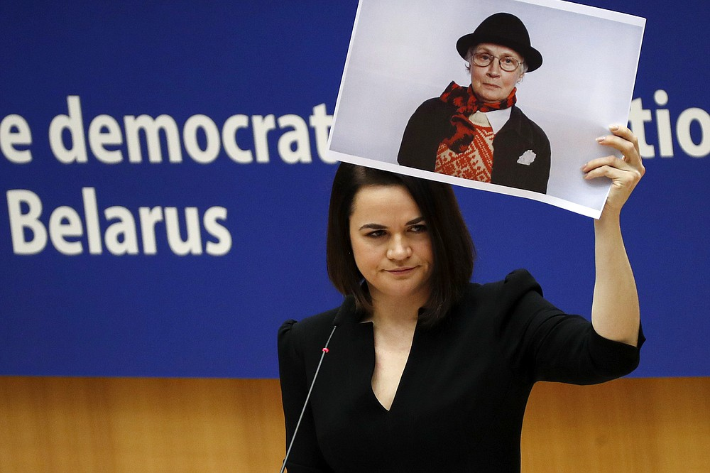 FILE In this file photo taken on Wednesday, Dec. 16, 2020, Belarusian opposition politician Sviatlana Tsikhanouskaya holds a picture of Belarusian opposition activist Nina Baginskaya as she gives a speech during the Sakharov Prize ceremony at the European Parliament in Brussels. A wave of COVID-19 has spread through Belarusian jails packed with people imprisoned for taking part in four months of protests against the nation's authoritarian president. Activists, who tested positive after being released, describe massively overcrowded cells and the lack of basic amenities, and some even allege that the authorities have deliberately spread contagion among political prisoners.  (AP Photo/Francisco Seco, File)