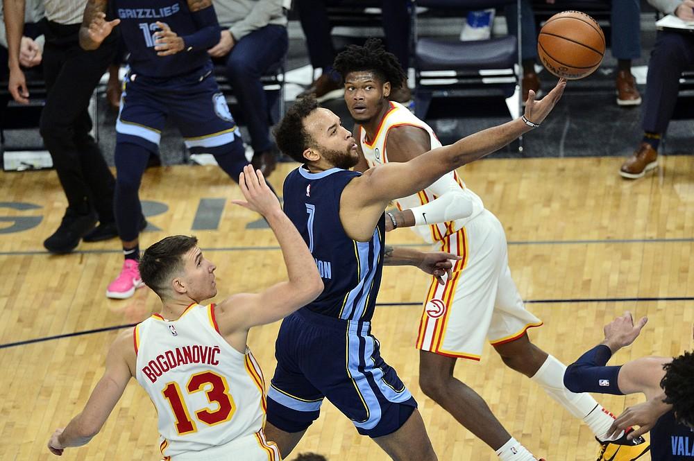Memphis Grizzlies forward Kyle Anderson (1) shoots between Atlanta Hawks guard Bogdan Bogdanovic (13) and forward Cam Reddish in the first half of an NBA basketball game Saturday, Dec. 26, 2020, in Memphis, Tenn. (AP Photo/Brandon Dill)