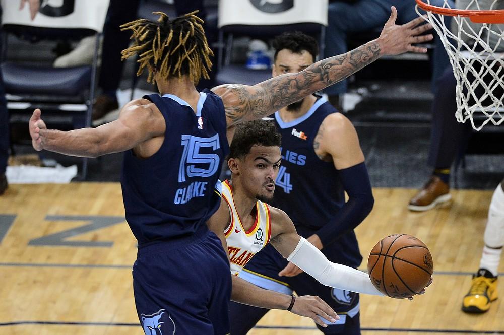 Atlanta Hawks guard Trae Young handles the ball between Memphis Grizzlies forward Brandon Clarke (15) and guard Dillon Brooks (24) during the second half of an NBA basketball game Saturday, Dec. 26, 2020, in Memphis, Tenn. (AP Photo/Brandon Dill)