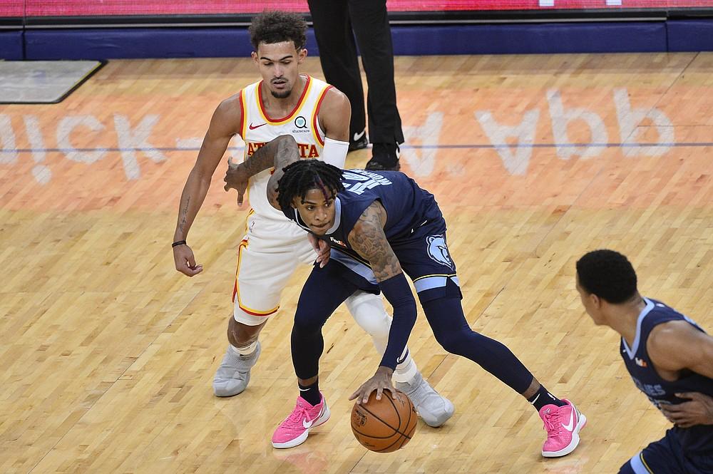 Memphis Grizzlies guard Ja Morant (12) handles the ball against Atlanta Hawks guard Trae Young in the first half of an NBA basketball game Saturday, Dec. 26, 2020, in Memphis, Tenn. (AP Photo/Brandon Dill)