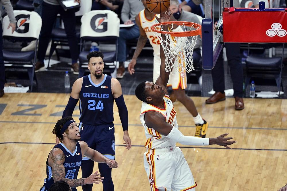 Atlanta Hawks forward Nathan Knight shoots ahead of Memphis Grizzlies forward Brandon Clarke (15) and guard Dillon Brooks (24) during the second half of an NBA basketball game Saturday, Dec. 26, 2020, in Memphis, Tenn. (AP Photo/Brandon Dill)