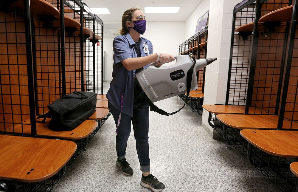 Hannah Huckabee, a custodian with Fayetteville Public Schools, uses a hospital-grade mister Dec. 15 to disinfect the Fayetteville High School volleyball team locker room. The cleaning procedure takes place after hours when no students are in the area. Check out nwaonline.com/201228Daily/ and nwadg.com/photos for a photo gallery. (NWA Democrat-Gazette/David Gottschalk)