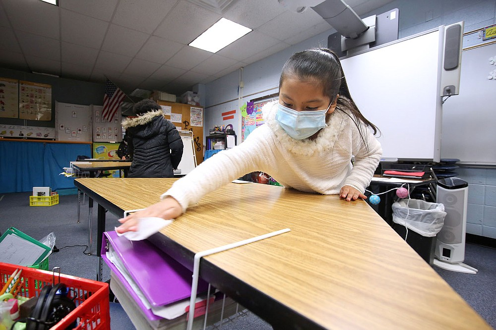Third-grader Mary Juarez wipes down her desk with an antibacterial wipe Dec. 11 at David O. Dodd Elementary in Little Rock.  Check out nwaonline.com/201228Daily/ and nwadg.com/photos for a photo gallery. (Arkansas Democrat-Gazette/Thomas Metthe)