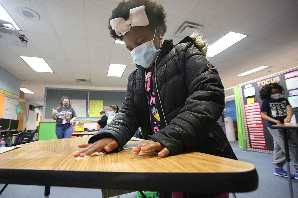 Third-grader Deaerial Hill wipes her desk down with an antibacterial wipe Dec. 11 at David O. Dodd Elementary in Little Rock.  Check out nwaonline.com/201228Daily/ and nwadg.com/photos for a photo gallery. (Arkansas Democrat-Gazette/Thomas Metthe)