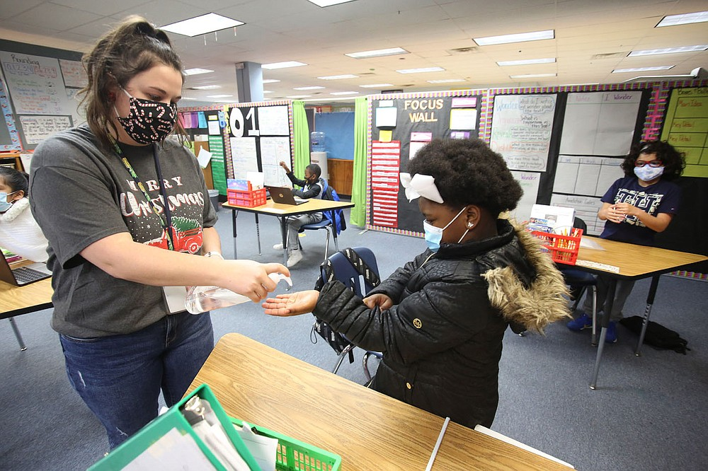Sarah McPherson, Dodd Elementary third-grade teacher at Dodd Elementary School, gives a squirt of hand sanitizer Dec. 11 to student Deaerial Hill after wiping down her desk at David O. Dodd Elementary in Little Rock.  Check out nwaonline.com/201228Daily/ and nwadg.com/photos for a photo gallery. (Arkansas Democrat-Gazette/Thomas Metthe)