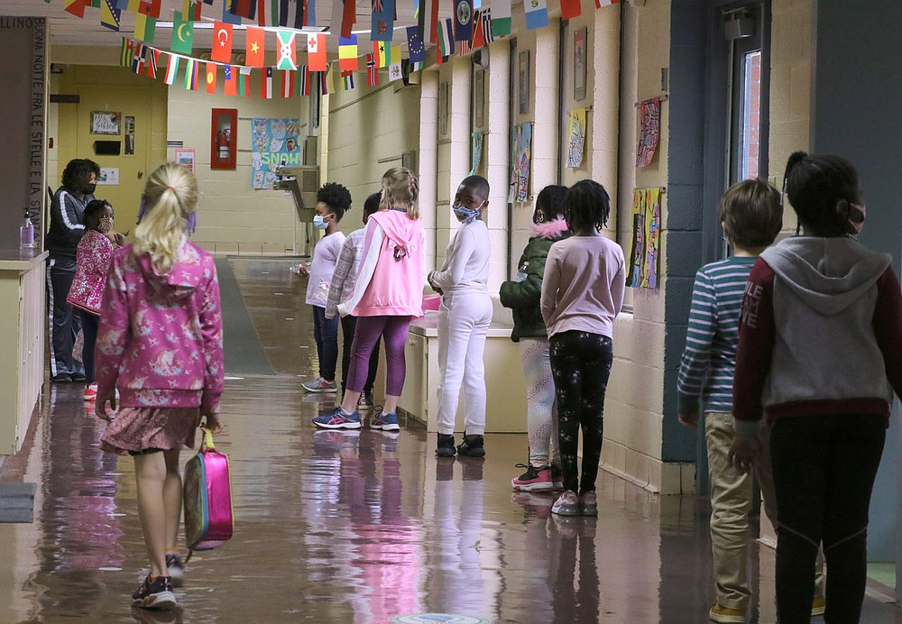 Second-grade students line up in the hallway Dec. 11 while maintaining social distance outside the cafeteria while waiting for for lunch at Gibbs Magnet Elementary School in Little Rock.  Check out nwaonline.com/201228Daily/ and nwadg.com/photos for a photo gallery. (Arkansas Democrat-Gazette/Thomas Metthe)