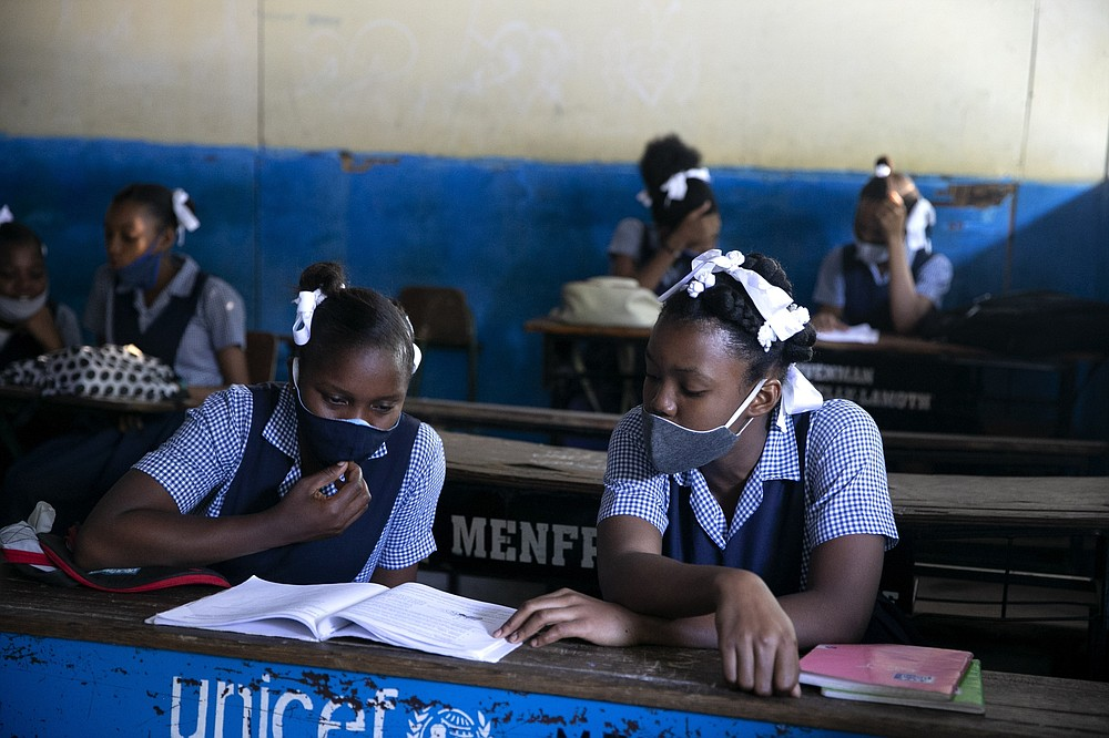 FILE - In this Aug. 17, 2020, file photo, students read at Lycee Marie Jeanne school in Port-au-Prince, Haiti, on their first day back to school amid the COVID-19 pandemic. Haiti, the Western Hemisphere's poorest country, has yet to announce any COVID-19 vaccination plans. Health experts worry that widespread rumors could set back vaccinations -- including claims that hospitals will give fatal injections to inflate COVID-19 death figures and receive more foreign aid. (AP Photo/Dieu Nalio Chery, File)