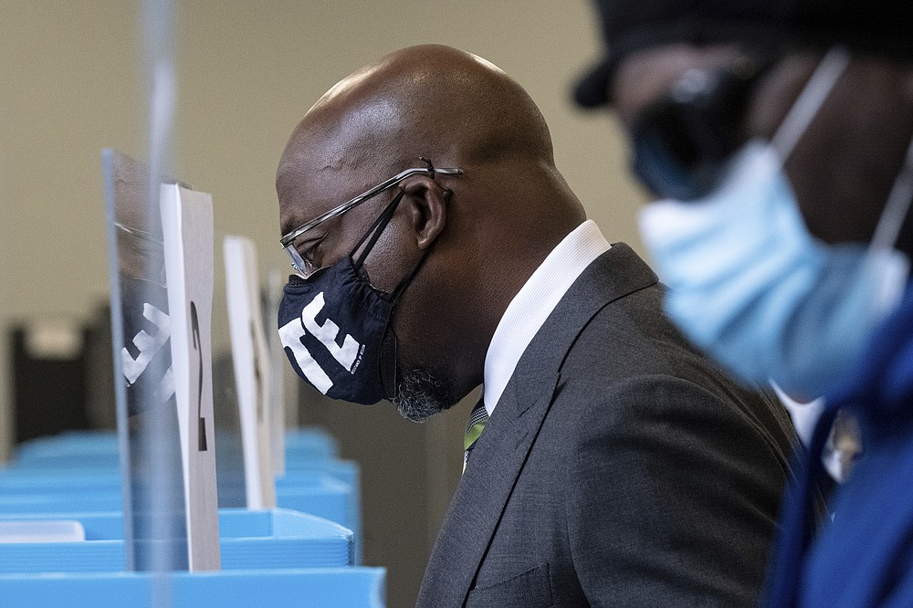 Democrat Georgia Senate challenger The Rev. Raphael Warnock checks in to vote at the C.T. Martin Natatorium and Recreation Center in Atlanta on the first day of early voting for the senate runoff Monday, Dec. 14, 2020. Early in-person voting began Monday in Georgia for the state's twin U.S. Senate runoffs. The early voting period runs as late as Dec. 31 in some counties. It could determine the outcome of the races between Republican U.S. Sens. David Perdue and Kelly Loeffler and Democratic challengers Jon Ossoff and Raphael Warnock. (AP Photo/Ben Gray)