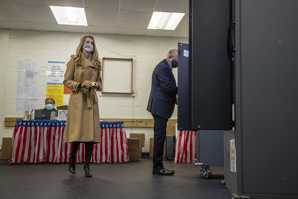 U.S. Sen. Kelly Loeffler, R-Ga., prepares to cast her ballot alongside her husband, Jeff Sprecher, right, during early voting in runoff elections at Chastain Park Gymnasium in Atlanta's Chastain Park neighborhood, Wednesday, Dec. 16, 2020. Democratic candidates Jon Ossoff and the Rev. Raphael Warnock are trying to to unseat Republican Sens. David Perdue and Kelly Loeffler in the runoff elections that will determine which party controls the Senate. (Alyssa Pointer/Atlanta Journal-Constitution via AP)