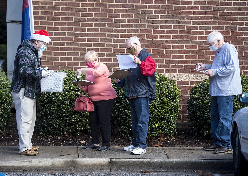 People wait in line on the first day of advance voting for Georgia's Senate runoff election at the Columbia County Government Complex in Evans, Ga., Monday, Dec. 14, 2020. Early in-person voting began Monday in Georgia for the state's twin U.S. Senate runoffs. The early voting period runs as late as Dec. 31 in some counties. It could determine the outcome of the races between Republican U.S. Sens. David Perdue and Kelly Loeffler and Democratic challengers Jon Ossoff and Raphael Warnock. (Michael Holahan/The Augusta Chronicle via AP)
