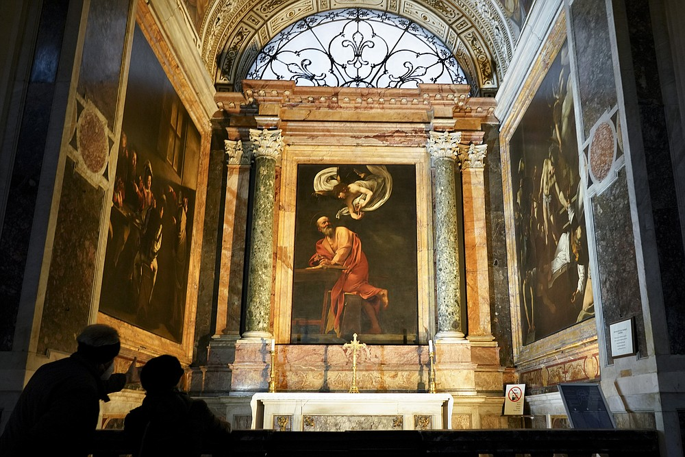 Visitors admire a cycle of paintings by 16th century artist Michelangelo Merisi, known as Caravaggio, on the life of St.Matthew, inside the Contarelli chapel of San Luigi dei Francesi Church, in Rome, Friday, Dec. 11, 2020. Like elsewhere in Europe, museums and art galleries in Italy were closed this fall to contain the spread of COVID-19, meaning art lovers must rely on virtual tours to catch a glimpse of the treasures held by famous institutions such as the Uffizi in Florence and the Vatican Museums in Rome. However, some exquisite gems of Italy's cultural heritage remain on display in real life inside the country's churches, some of which have collections of renaissance art and iconography that would be the envy of any museum. (AP Photo/Andrew Medichini)
