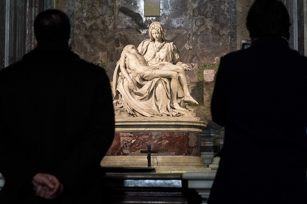 """Visitors admire the marble sculpture """"The Pietà,"""" made in 1499 by Italian sculptor Michelangelo Buonarroti, inside St. Peter's Basilica, at the Vatican. (AP/Andrew Medichini)"""