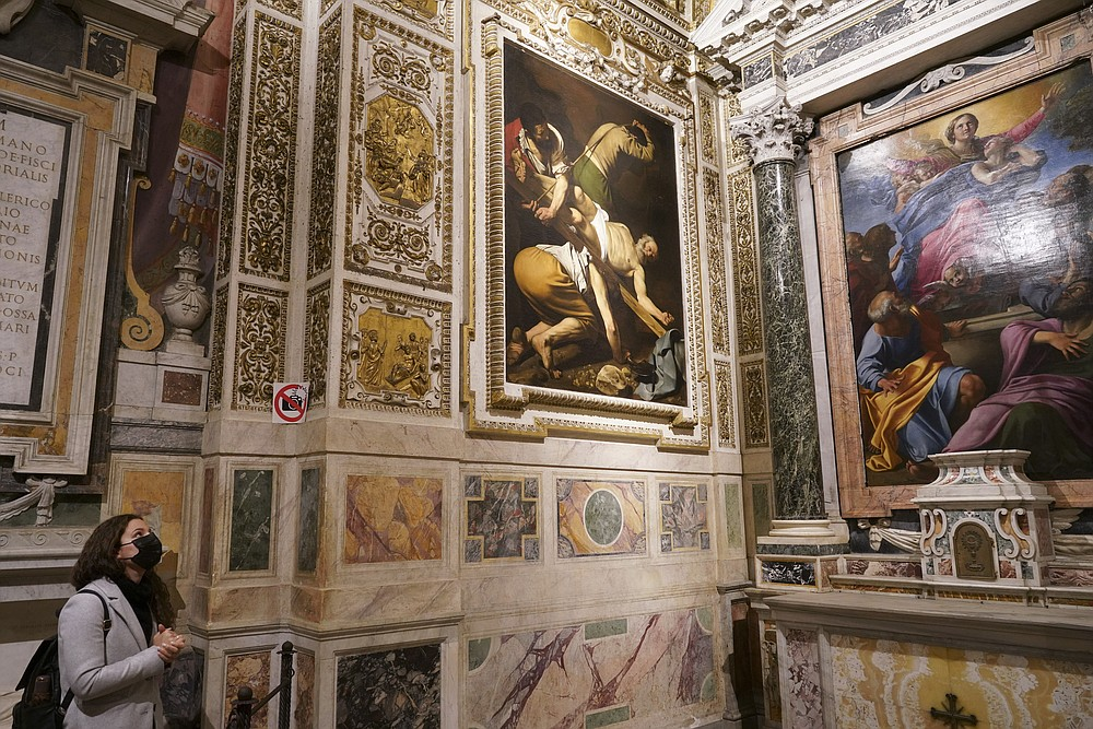 """A woman wearing a face mask to curb the spread of COVID-19 admires paintings he Cerasi Chapel of Santa Maria del Popolo church, Rome, Friday, Dec. 11, 2020. At left is """"The Crucifixion of St. Peter"""", 1601, by Renaissance master Michelangelo Merisi, known as Caravaggio, and at right, """"The Assumption of the Virgin"""", 1601, by Annibale Carracci. Like elsewhere in Europe, museums and art galleries in Italy were closed this fall to contain the spread of COVID-19, meaning art lovers must rely on virtual tours to catch a glimpse of the treasures held by famous institutions such as the Uffizi in Florence and the Vatican Museums in Rome. However, some exquisite gems of Italy's cultural heritage remain on display in real life inside the country's churches, some of which have collections of renaissance art and iconography that would be the envy of any museum. (AP Photo/Andrew Medichini)"""