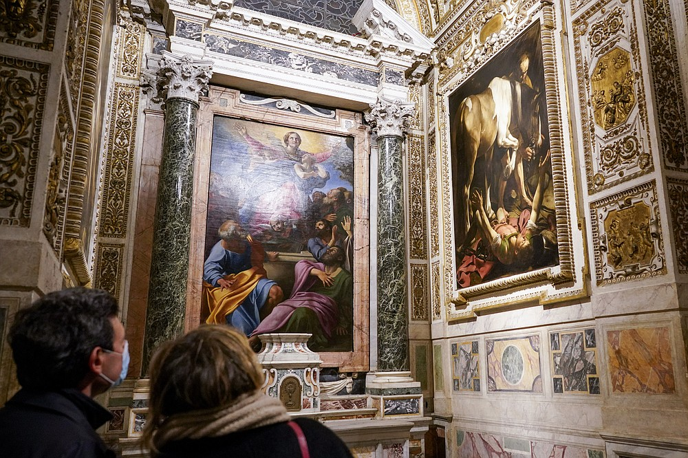 """Visitors admire the """"Conversion (of St. Paul) on the Way to Damascus"""", 1601, right, by Renaissance master Michelangelo Merisi, known as Caravaggio of 1601, flanking """"The Assumption of the Virgin"""", 1601, by Annibale Carracci, inside the Cerasi Chapel of Santa Maria del Popolo church, Rome, Friday, Dec. 11, 2020. Like elsewhere in Europe, museums and art galleries in Italy were closed this fall to contain the spread of COVID-19, meaning art lovers must rely on virtual tours to catch a glimpse of the treasures held by famous institutions such as the Uffizi in Florence and the Vatican Museums in Rome. However, some exquisite gems of Italy's cultural heritage remain on display in real life inside the country's churches, some of which have collections of renaissance art and iconography that would be the envy of any museum. (AP Photo/Andrew Medichini)"""