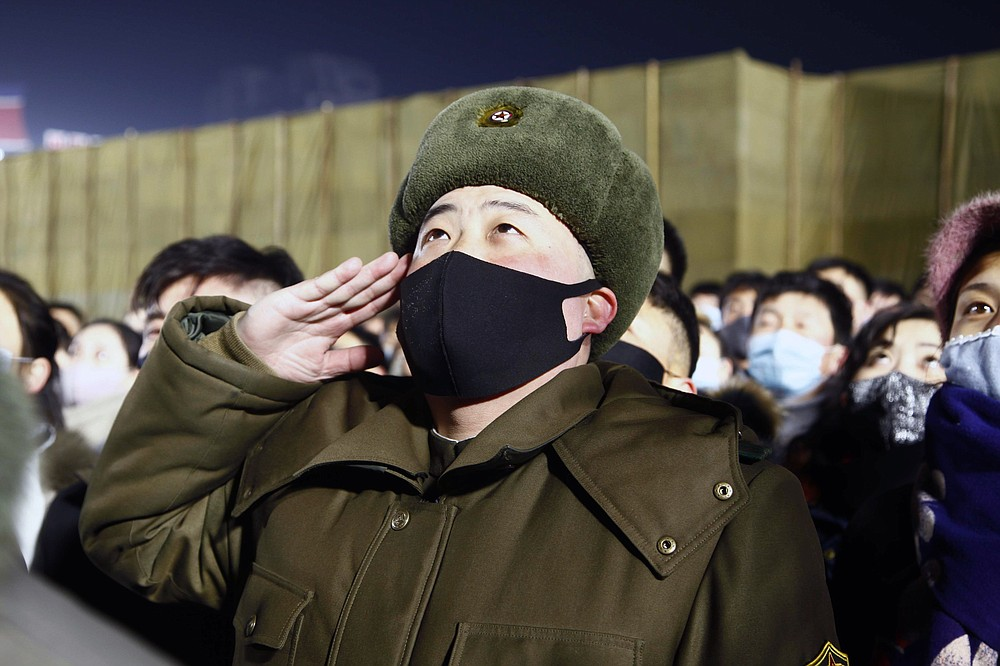 A man salutes during the national flag-hoisting ceremony during celebrations to mark the New Year, at Kim Il Sung Square in Pyongyang, North Korea, early Friday, Jan., 1, 2021. (AP Photo/Jon Chol Jin)