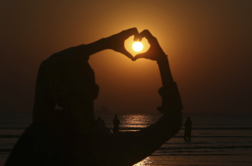 A boy make heart sign while the last sunset of 2020 hangs over the Sindh's provincial capital of Karachi, Pakistan, Thursday, Dec. 31, 2020. (AP Photo/Fareed Khan)