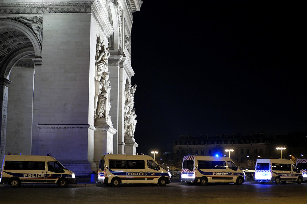Police vans are parked near the Arc of Triomphe, ahead of the New Year's Eve, in Paris, Thursday, Dec. 31, 2020. As the world says goodbye to 2020, there will be countdowns and live performances, but no massed jubilant crowds in traditional gathering spots like the Champs Elysees in Paris and New York City's Times Square this New Year's Eve. (AP Photo/Thibault Camus)