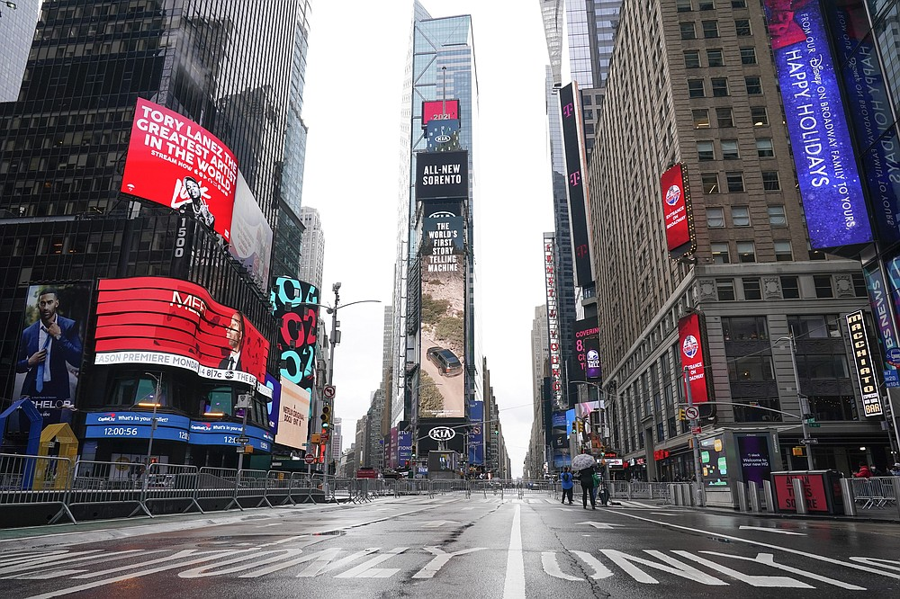 Pedestrians walk in a nearly empty Times Square ahead of the New Year's Eve celebration Thursday, Dec. 31, 2020, in New York. (AP Photo/Frank Franklin II)