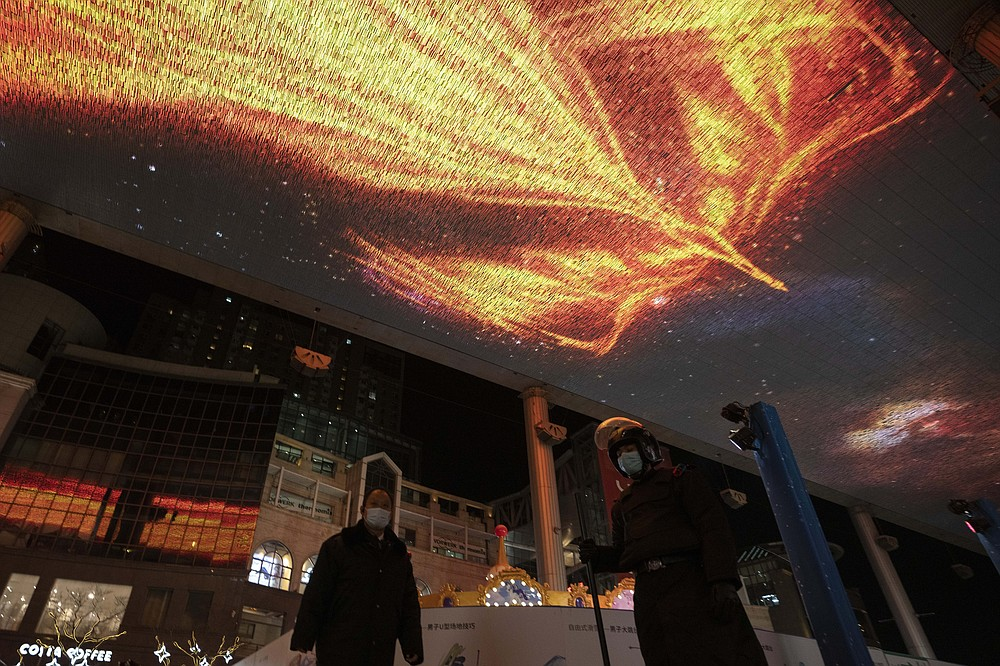 A security guard stands on duty as a phoenix is shown on a giant screen on New Year Eve in Beijing Thursday, Dec. 31, 2020. This New Year's Eve is being celebrated like no other, with pandemic restrictions limiting crowds and many people bidding farewell to a year they'd prefer to forget. (AP Photo/Ng Han Guan)