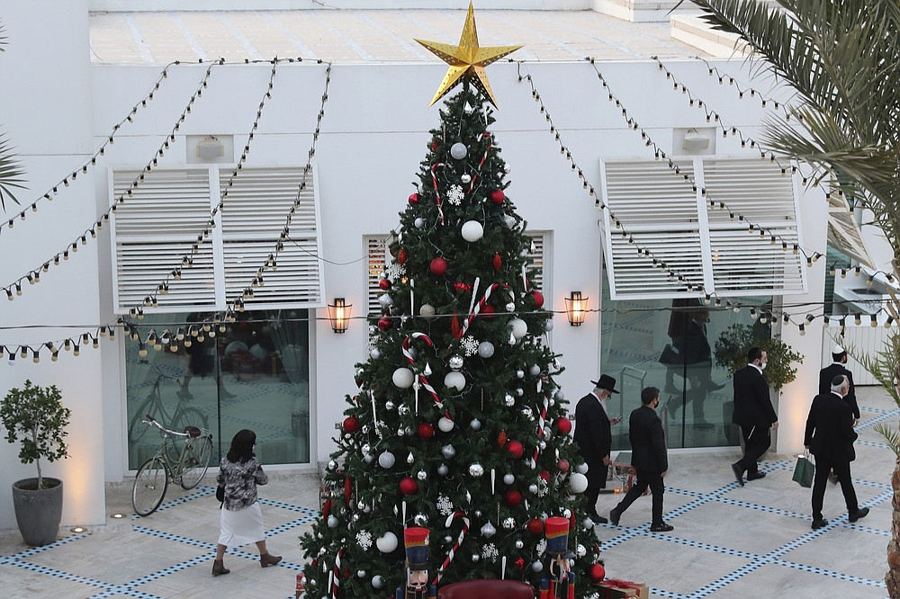 A rabbi and other guests pass a Christmas tree to take part in an Israeli wedding ceremoney in Dubai, United Arab Emirates, Thursday, Dec. 17, 2020.  For the past month, Israelis long accustomed to traveling incognito, if at all, to Arab countries, have made themselves at home in the UAE's commercial hub. (AP Photo/Kamran Jebreili)