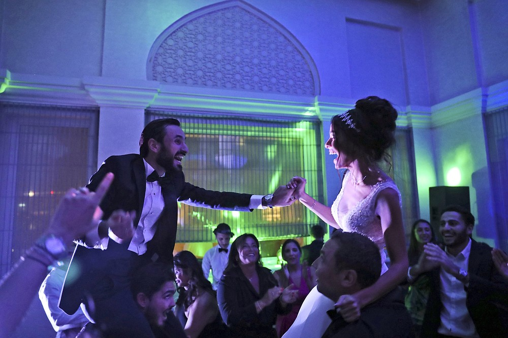 Israeli couple Noemie Azerad, right, and her husband Simon David Benhamou grasp each others hands on the shoulders of skullcap-wearing groomsmen during their wedding party at a hotel in Dubai, United Arab Emirates, Thursday, Dec. 17, 2020.  For the past month, Israelis long accustomed to traveling incognito, if at all, to Arab countries, have made themselves at home in the UAE's commercial hub.(AP Photo/Kamran Jebreili)