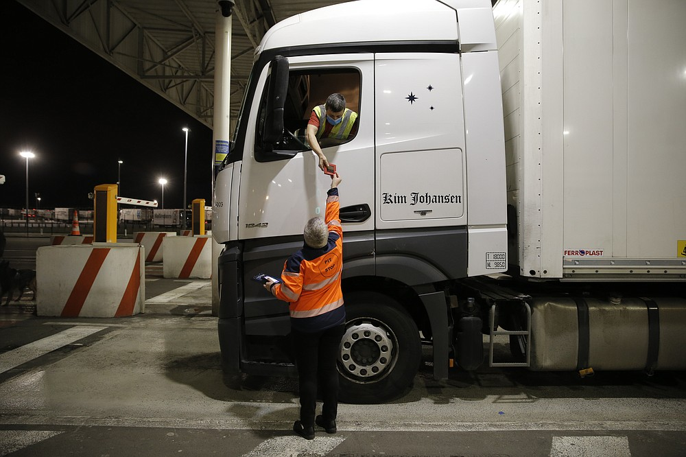 A man gives a document to the driver of the first truck, from Estonia, entering the Eurotunnel terminal Friday, Jan.1, 2021 in Coquelles, northern France. Eleven months after Britain's formal departure from the EU, Brexit becomes a fact of daily life on Friday, once a transition period ends and the U.K. fully leaves the world's most powerful trading bloc. (AP Photo/Lewis Joly, Pool)