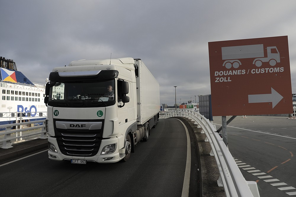 A lorry arrives to board the first ferry heading to Britain after Brexit, Friday Jan.1, 2021 in Calais, northern France. Britain left the European bloc's vast single market for people, goods and services at 11 p.m. London time, midnight in Brussels, completing the biggest single economic change the country has experienced since World War II. (AP Photo/Lewis Joly)