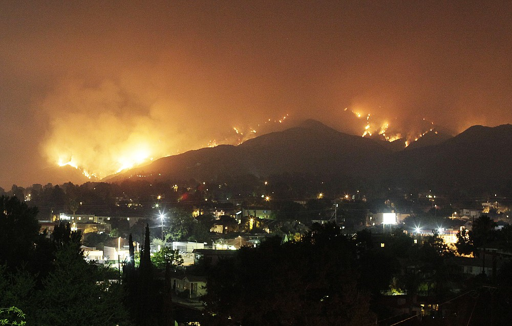FILE - In this Monday, Aug. 31, 2009 file photo, wildfires rage on the hillsides of the Tujunga area of Los Angeles in the Station fire. (AP Photo/John Lazar)