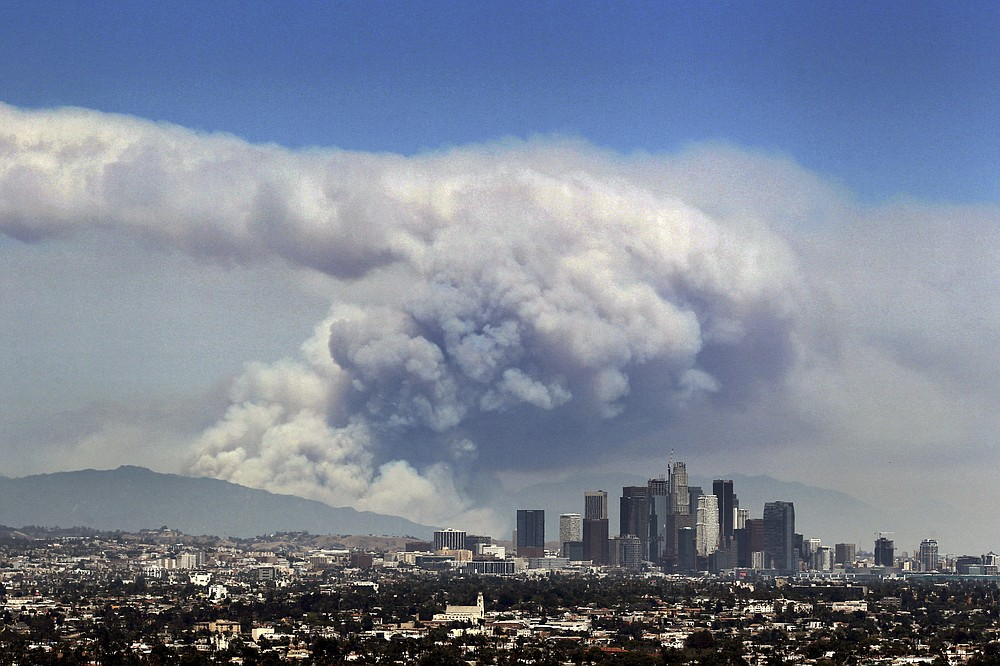 FILE - In this Monday, June 20, 2016 file photo, smoke from wildfires burning in Angeles National Forest fills the sky behind the Los Angeles skyline. The Federal Emergency Management Agency has calculated the risk for every county in America for 18 types of natural disasters, such as earthquakes, hurricanes, tornadoes, floods, volcanos and even tsunamis. And of the more than 3,000 counties, Los Angeles County has the highest ranking in theNational Risk Index. (AP Photo/Ringo H.W. Chiu)