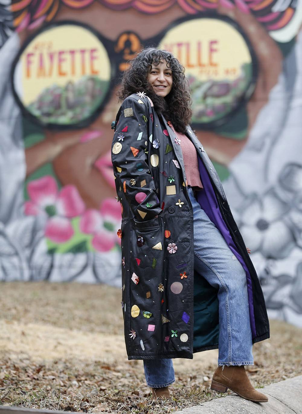 Designer Brandy Lee displays an up-cycled leather coat featuring leather cutouts, rhinestone and leather flowers Tuesday, Dec. 29, 2020, outside of her studio in Fayetteville. The Arkansas Arts and Fashion Forum said the pandemic has caused the need for changing how the industry operates, to include creating more of a reliance on American-made products and processes that will prevent lags in the industry in the future. Lee is creating a collection of jackets that she will be releasing after the first of the year. Check out nwadg.com/photos for a photo gallery. (NWA Democrat-Gazette/David Gottschalk)