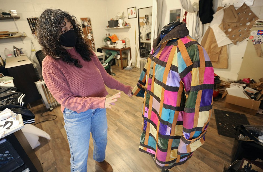 Designer Brandy Lee displays one of her coats Tuesday, Dec. 29, 2020, at her studio in Fayetteville. The Arkansas Arts and Fashion Forum said the pandemic has caused the need for changing how the industry operates, to include creating more of a reliance on American-made products and processes that will prevent lags in the industry in the future. Lee is creating a collection of jackets that she will be releasing after the first of the year. Check out nwadg.com/photos for a photo gallery. (NWA Democrat-Gazette/David Gottschalk)